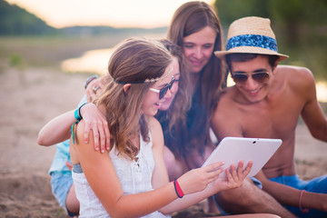 teenagers having fun at the beach watching pictures on tablet