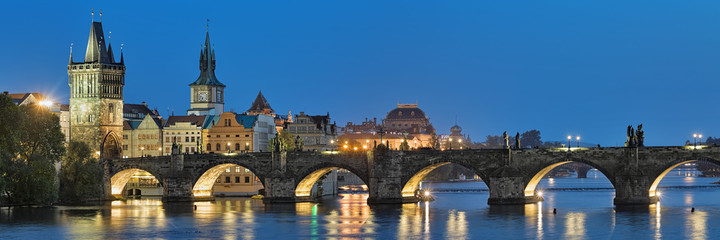 Evening panorama of the Charles Bridge in Prague, Czech Republic, with Old Town Bridge Tower, Old Town Water Tower and dome of the National Theatre