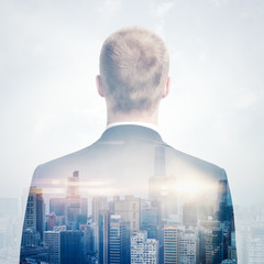 Double exposure portrait of a businessman looking cityscape