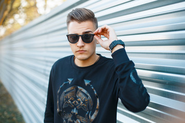 Young handsome man in sunglasses in the autumn sunny day on the background of metal wall.