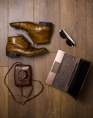 brown shoes, belt, bag and film camera with laptop