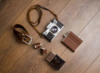 Vintage camera and leather belt on wooden floor