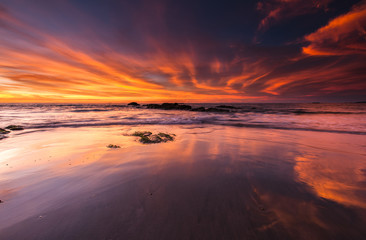 orange sunset with reflection on wet sand