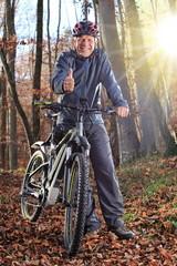 Senior neben E Mountainbike Wald Daumen hoch