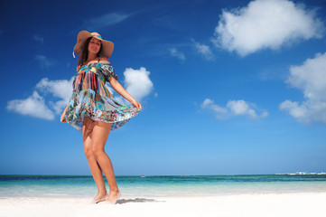 Carefree woman dancing on the tropical beach. vacation vitality