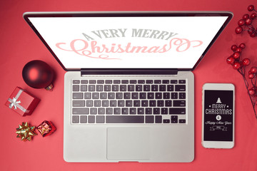 Laptop computer and smartphone with Christmas decorations. Christmas mock up template. View from above