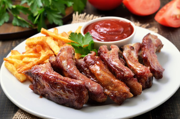 Pork ribs, potato fries and tomato sauce, close up view