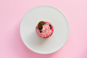 Pink decorated cupcake on white cake stand and pink background, top view, minimal style.