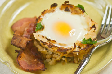 Egg in Potato Nest with Bacon, parsley on yellow plate and fork