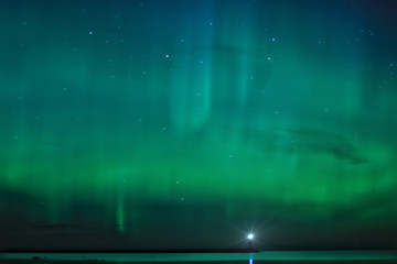Landscape with Aurora Borealis over the Ladoga Lake and a lighthouse