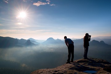 Two friends. Hiker thinking and photo enthusiast takes photos  stay on cliff. Dreamy fogy landscape, blue misty sunrise in a beautiful valley below