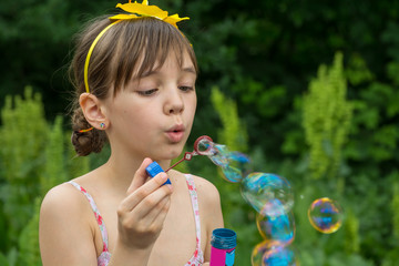 Little girl inflates soap bubbles in the garden