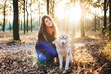 young happy female having fun with siberian husky dog in autumn park during sunset
