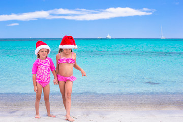 Little cute girls in Santa hats having fun during Christmas beach vacation
