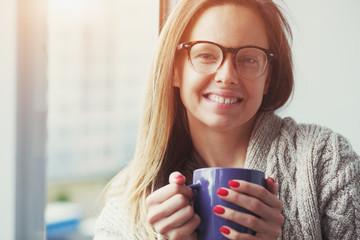 cheerful girl drinking coffee or tea in morning sunlight