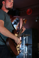 Young man playing on electric guitar at pub
