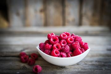 Fresh raspberries on rustic wooden background