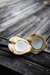 Halved coconut on wooden background