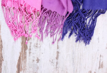 Colorful scarves with copy space for text, old rustic wooden background