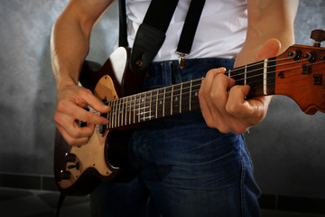 Young man paying guitar closeup