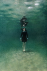 Girl in black dress underwater