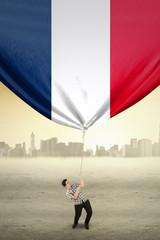 Man pulling flag of France