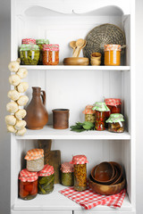 Jars with pickled vegetables and beans, spices,  kitchenware and utensils on shelf