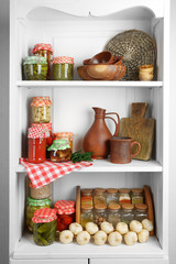 Jars with pickled vegetables and beans, spices, book of recipes and kitchen utensils on shelves of cupboard