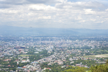 View of Chiang Mai city from a view point on Doi Suthep mountain as a plane takes off from Chiang Mai airport