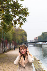 Beautiful girl listening to music with headphones in an urban co