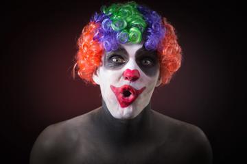 Evil Spooky Clown Portrait on dark background. expressive man