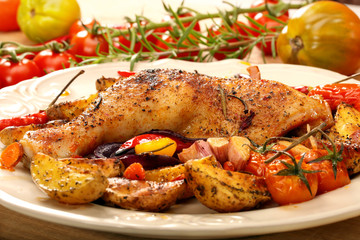 Roasted chicken legs with vegetables and herbs on wooden backgro