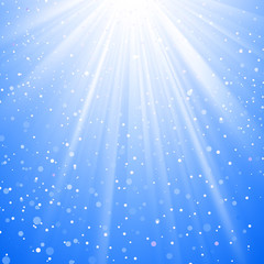 Shining sunbeams from above with snow flakes