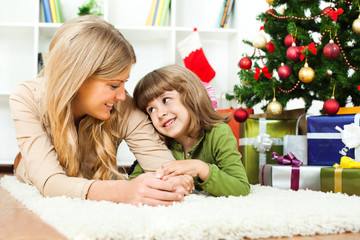 Happy mother and daughter with new year's tree and gift boxes