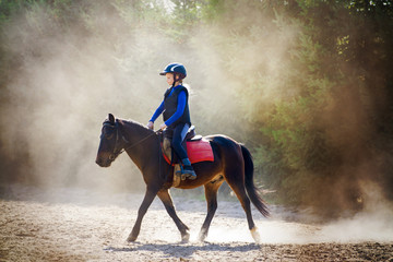 A young girl riding her pony during riding lesson, outside. Natural sun rays shining in dust during...