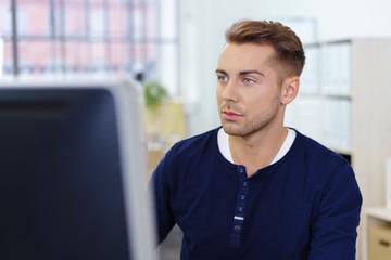 junger mann im büro schaut konzentriert auf computer