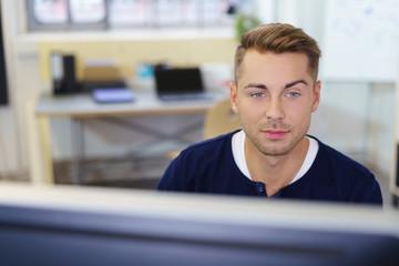 mann im büro schaut interessiert auf computer