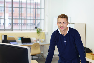 lächelnder angestellter steht im büro am schreibtisch