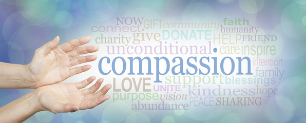 Compassion banner -  wide banner with a woman's hands in an open needy position with the word COMPASSION to the right surrounded by a relevant word cloud on a soft blue and white bokeh background
