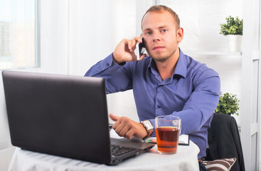 Young businessman working in office, sitting at a table, looking straight and talking on the phone
