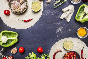 tortilla with Ingredients for cooking vegetarian burrito with vegetables and lime on wooden rustic background top view close up  with text area