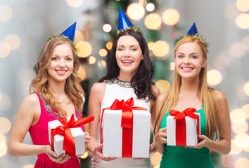 smiling women in party caps with gift boxes