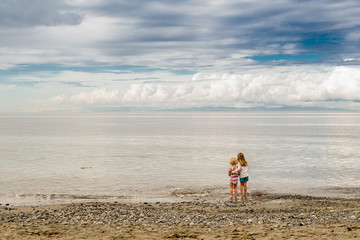 Rear view of Two girls standing on beach