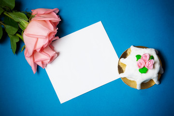 Pink roses, card  and cake with pink  marzipan roses on blue background