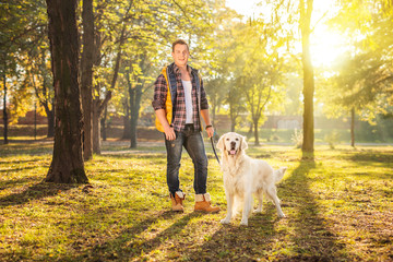 Man standing in a meadow and posing with a dog