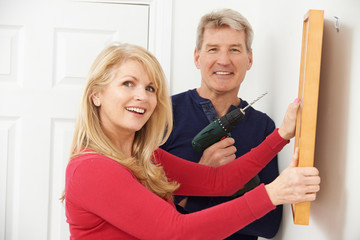 Portrait Of Mature Couple Drilling Wall To Hang Picture Frame