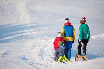 Junge Familie beim Schlittenfahren im Winter
