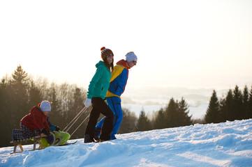 Familie im Winter beim Schlittenfahren