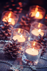 Christmas and New Year's background with candles, fir cones and