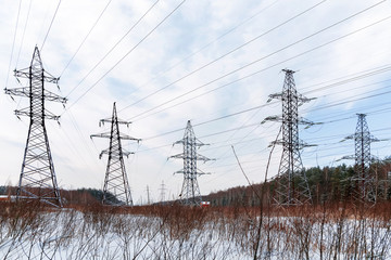 Power line in a winter forest. Electric equipment stays in snowy field.